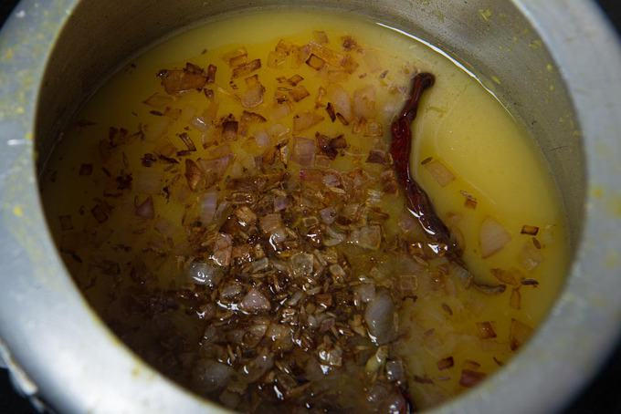 Tempering of browned onion and ginger poured over the dal in the pressure cooker