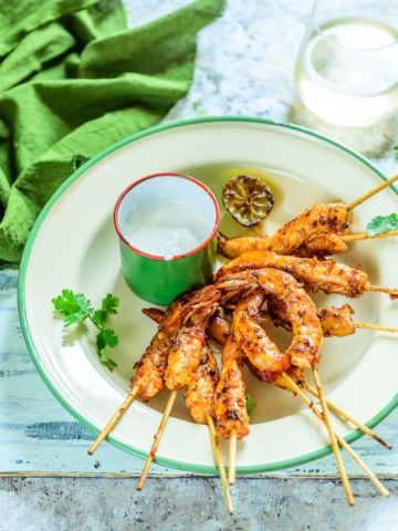 Grilled Sambal Prawns are pungent munchies made using prawns marinated with sambal paste which are grilled using skewers. Serve them for supper or as sides.