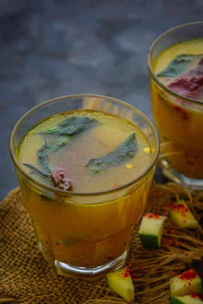 mango rasam served in a glass.