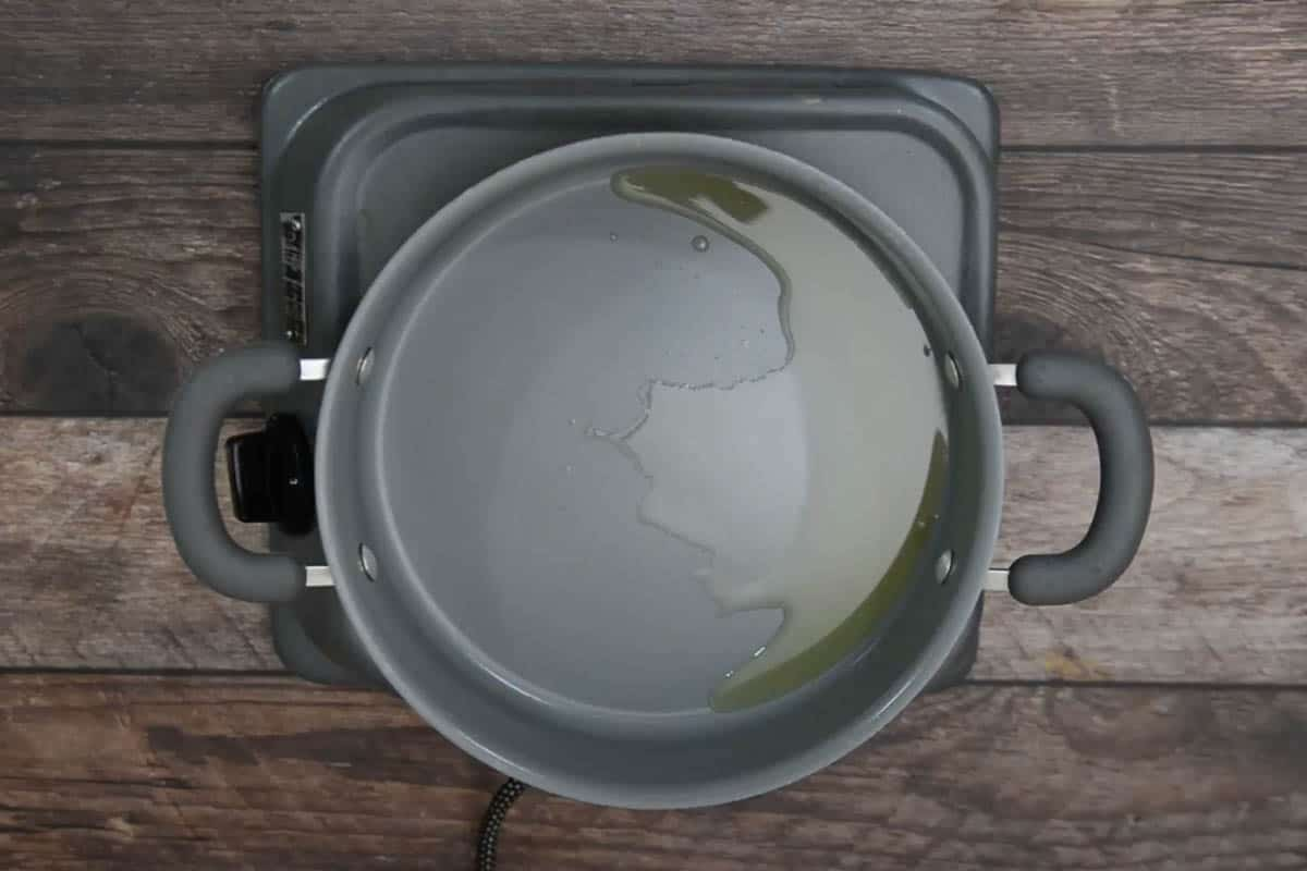 Olive oil heating in a pan.