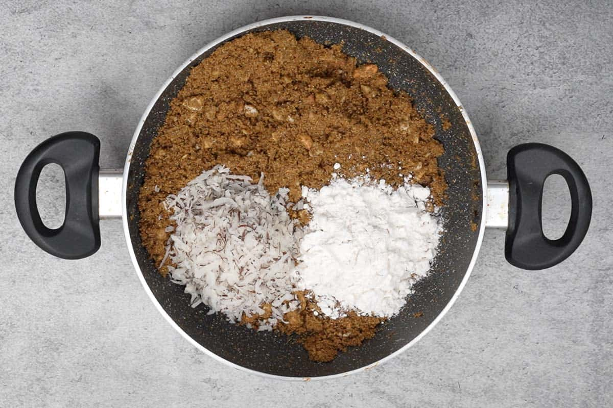 Grated dry coconut and powdered sugar added to the pan.