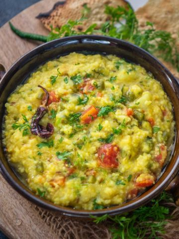 Daliya Khichdi, also known as Broken Wheat Khichdi or Fada ni Khichdi, is healthy Indian comfort food made using yellow lentil and broken wheat. Here is how to make it.