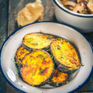 Bengali Begun Bhaja is a dish prepared out of thick slices of the eggplant marinated in spices and coated with rice flour and deep fried.
