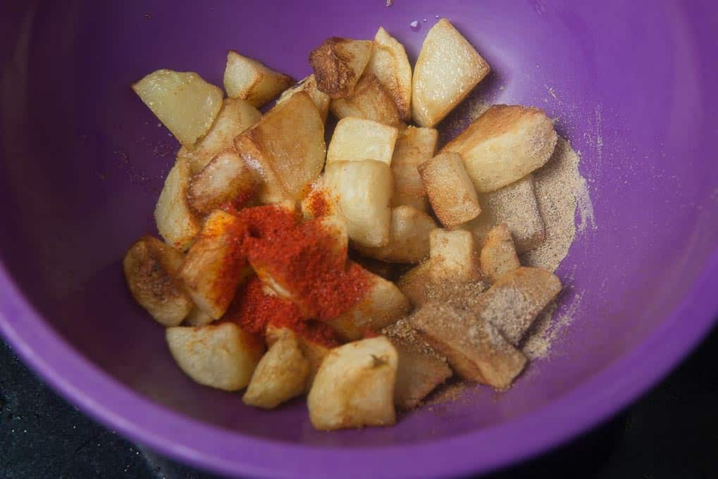 Dry spices and lemon juice added in potato cubes in a bowl