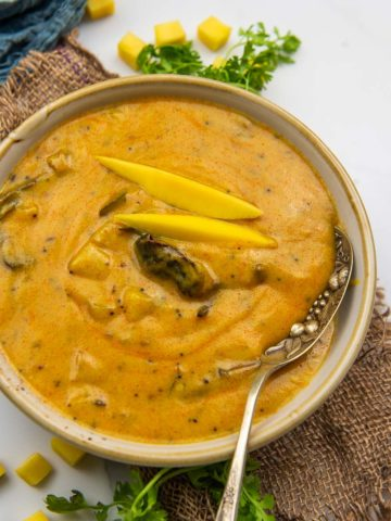 Your traditional kadhi gets an interesting twist of raw green mangoes! This spicy tangy green mango kadhi needs simple pantry ingredients and comes together in 30 minutes. Here is how to make it.