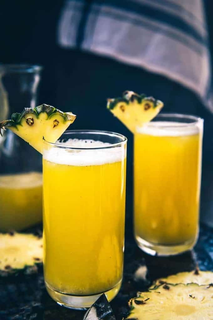 Homemade Fresh Pineapple Juice served in two glasses garnished with pineapple wedges.
