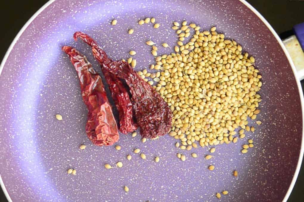 Coriander seeds and dry red chillies roasting in a pan