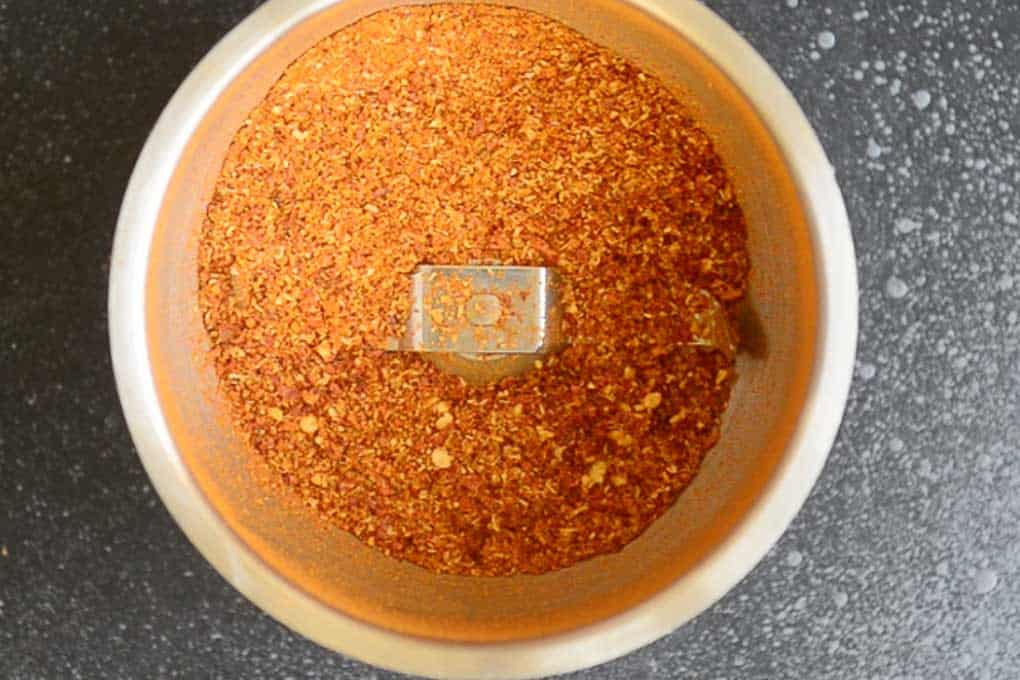 Powdered coriander seeds and red chillies in a blender