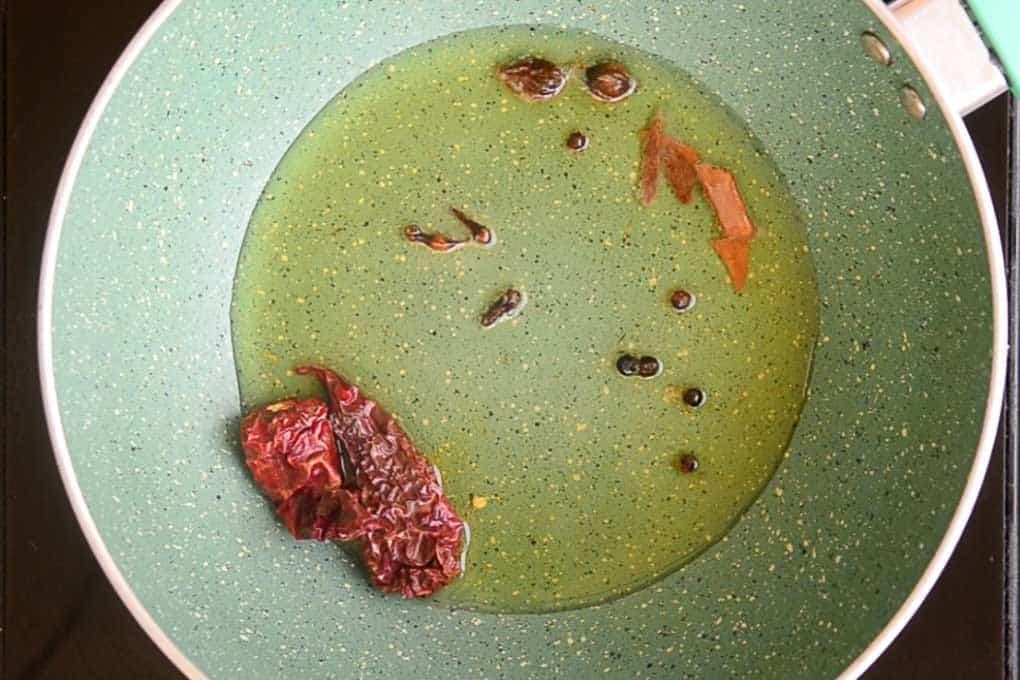 Dry red chillies and whole garam masala in the heated oil in the pan