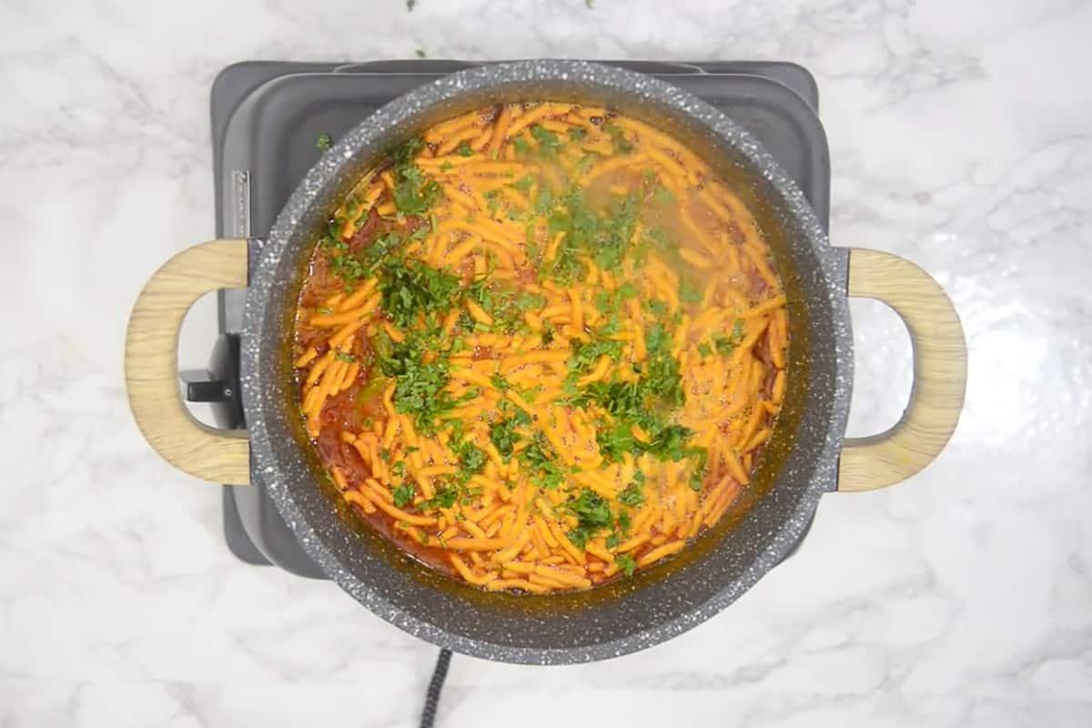 Sev Tamatar ki Sabji garnished with fresh coriander.