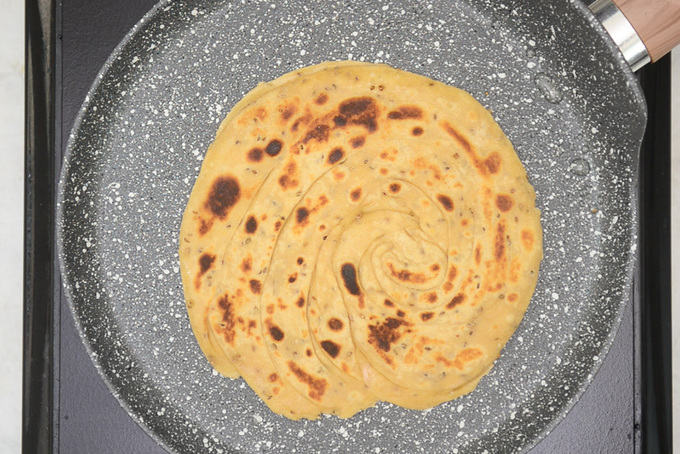 Paratha cooked on hot griddle.