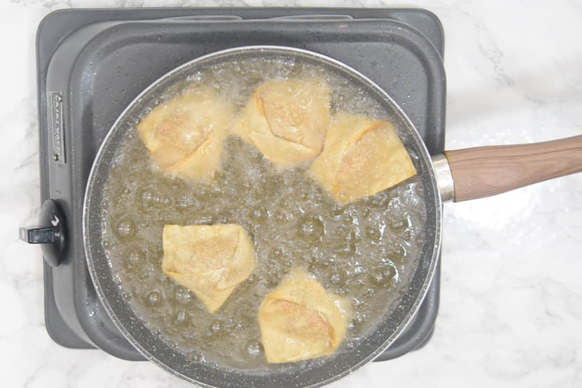 Crab Rangoon frying in hot oil.