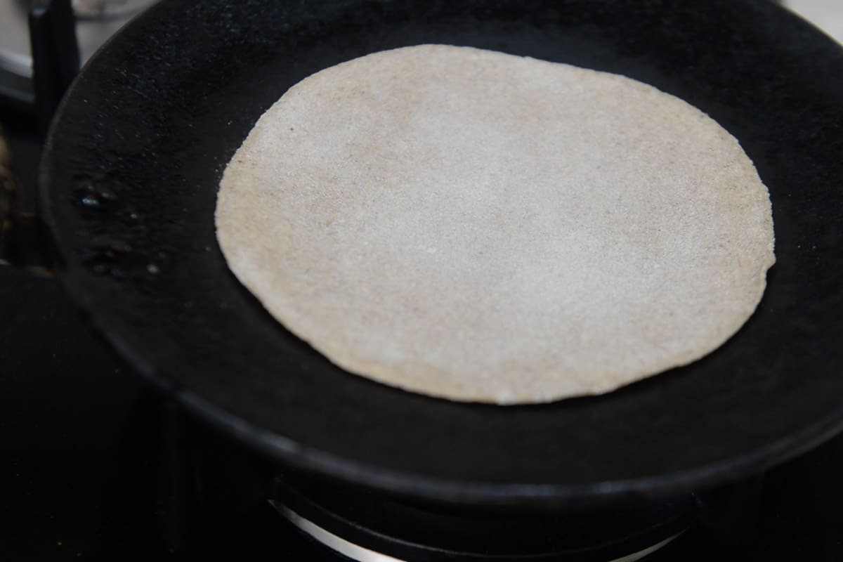 Roti transferred on a hot griddle.