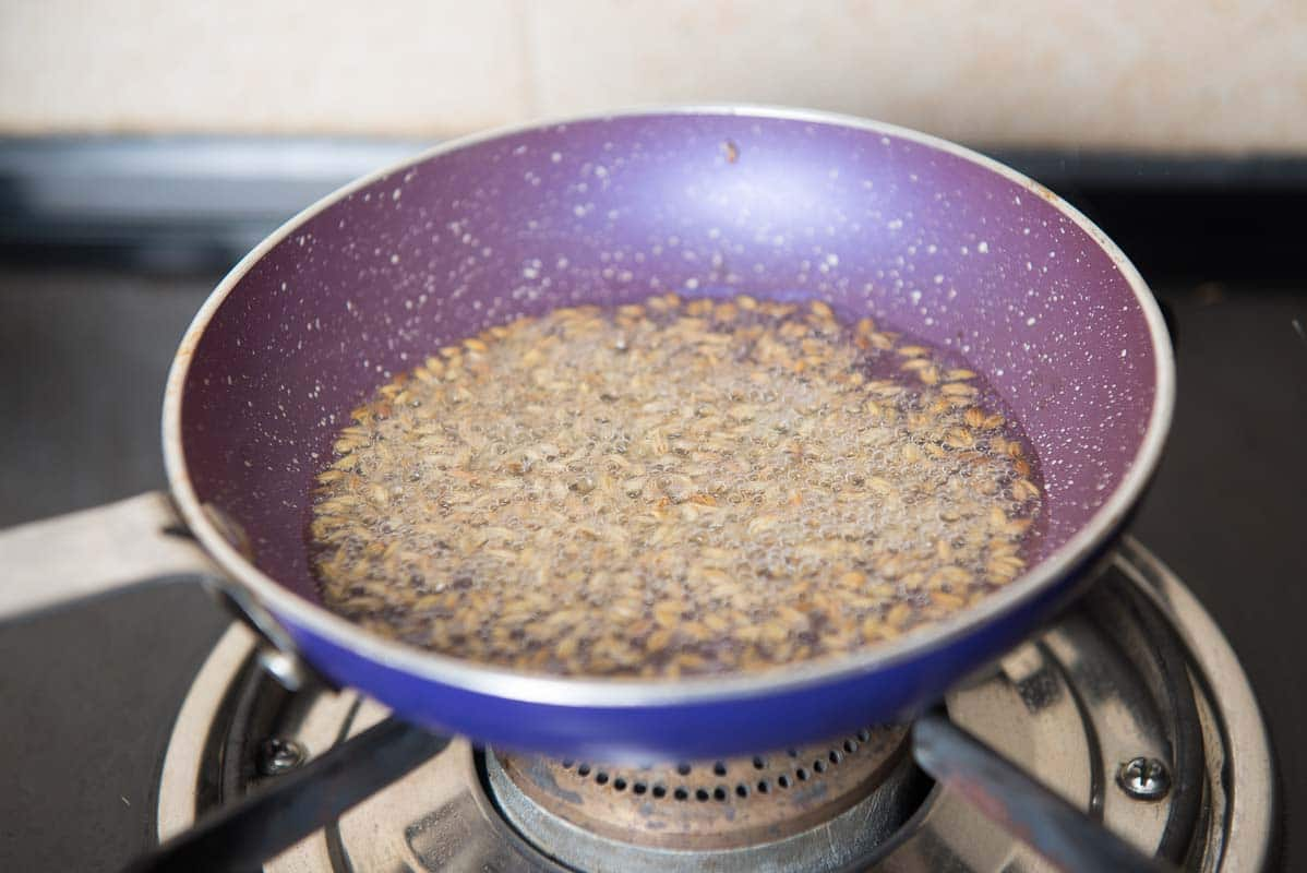 Once the ghee is hot, add cumin seeds and let them crackle for a few seconds.