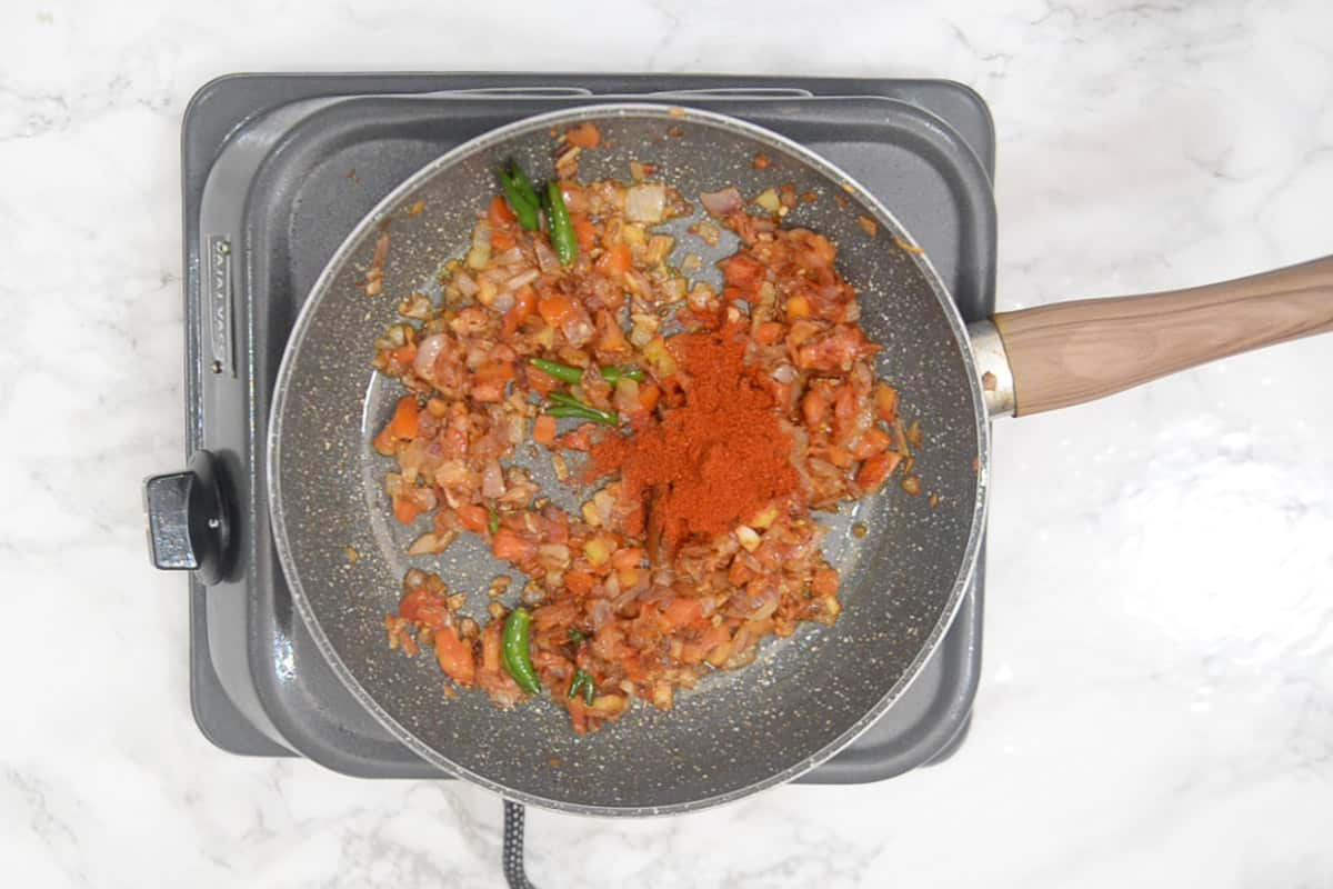 Red chilli powder added in the pan.