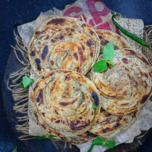 Pudina Parathaor Mint Paratha as the name suggests is made using dry mint powder and wheat flour and has many layers in it. This Indian bread goes very well with Indian curries.