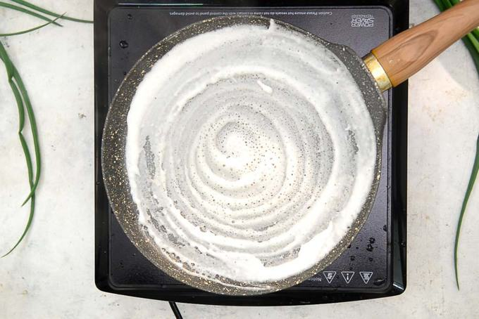 Dosa Batter spread over the pan.
