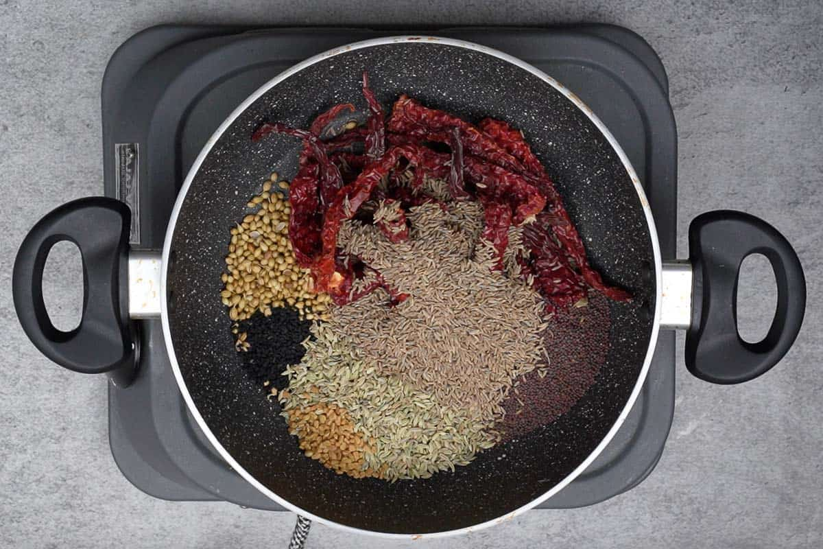 Dry red chilies, coriander seeds, nigella seeds, fennel seeds, mustard seeds, fenugreek seeds and cumin seeds added to a pan.