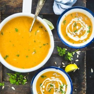 Top view of Carrot Ginger Soup in a pan and soup bowls