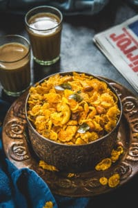Corn Flakes Chivda served in a metal bowl along with tea