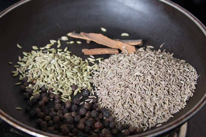 Cumin seeds, black pepper, fennel seeds and cinnamon dry roasting in a pan
