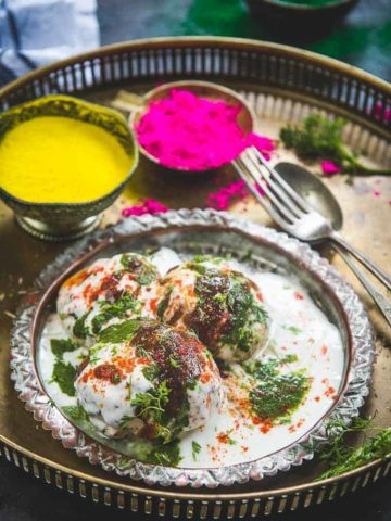 Side shot of dahi vada served ina plate along with holi colours.