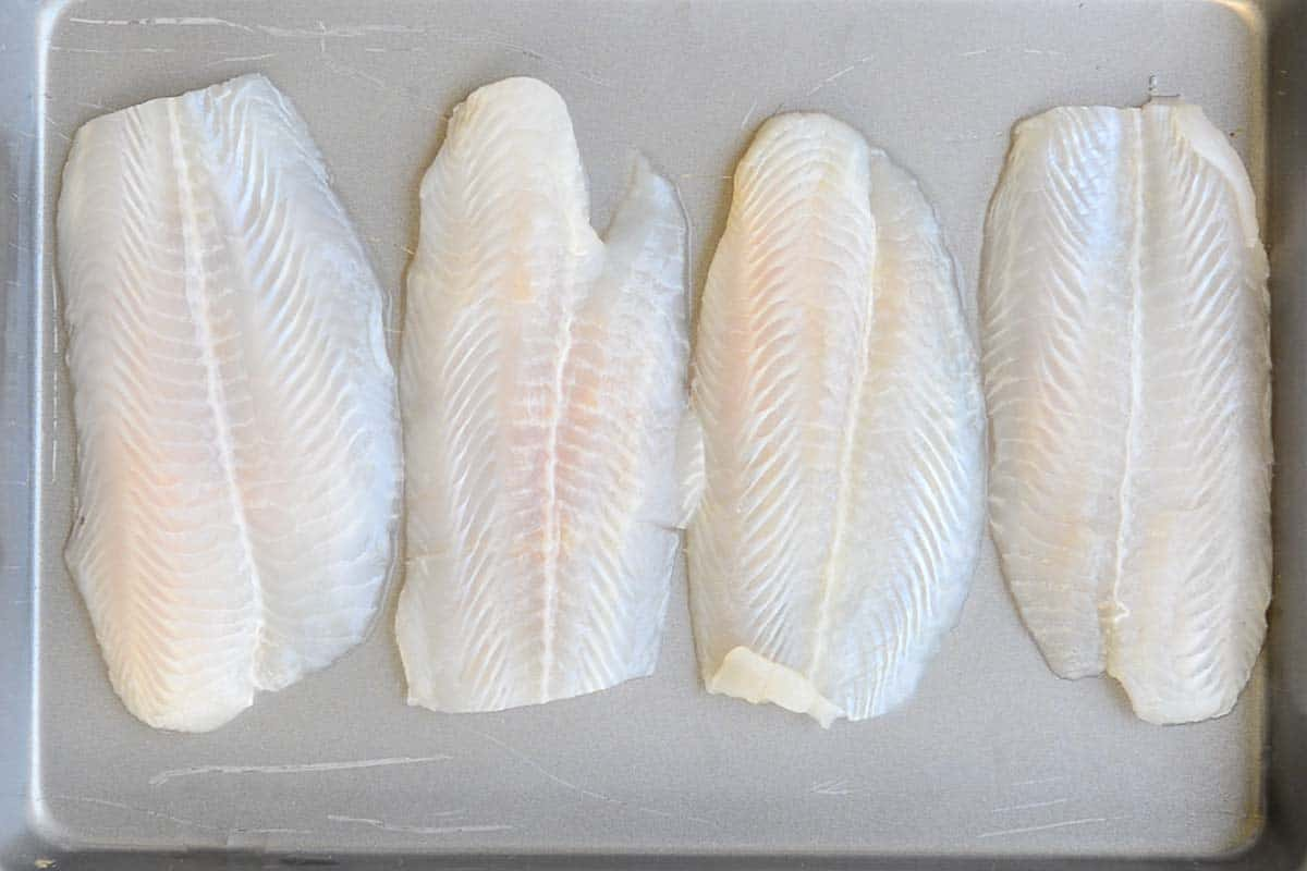 Top view of 4 basa Fish Fillets arranged on a baking tray.