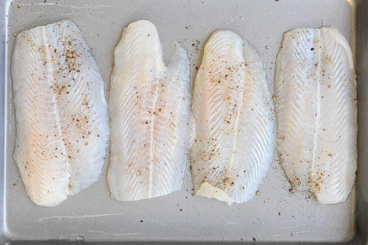 Top view of the basa fish fillets sprinkled with salt and pepper powder.