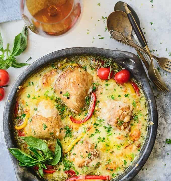 Creamy baked pesto chicken thighs in a serving pan.