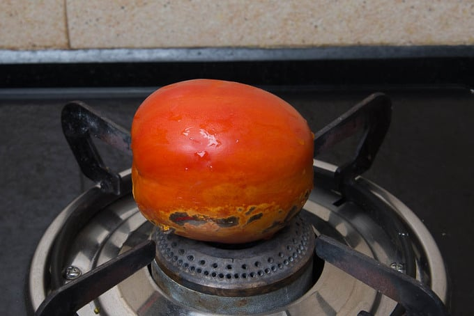 Fresh Tomato roasting on fire.