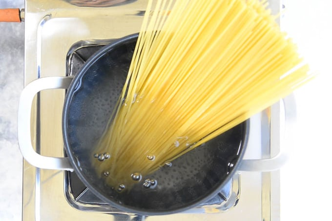 Spaghetti added in salted water in a pan