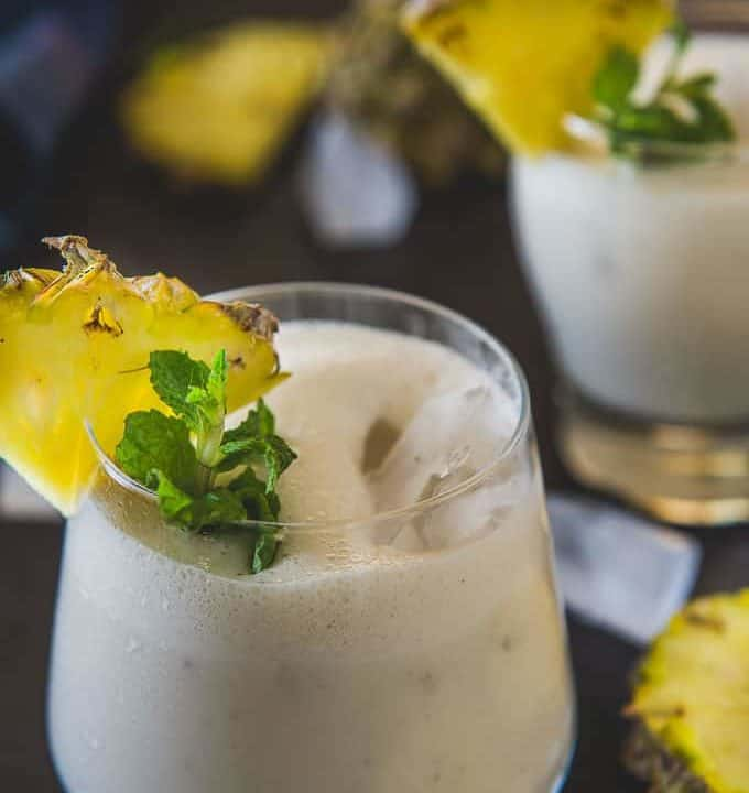 Pineapple Banana smoothie served in glasses garnished with pineapple wedge and mint leaves.