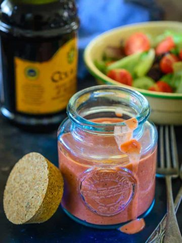Easy Balsamic Strawberry Vinaigrette recipe served ina galss jar along with salad in the background.