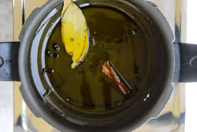 Whole spices added in oil in pressure cooker.