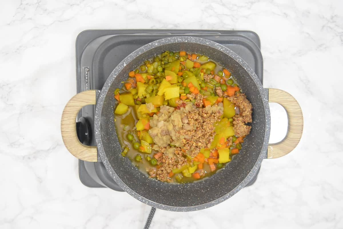Cooked dal, vegetables and masala paste added in a pan.
