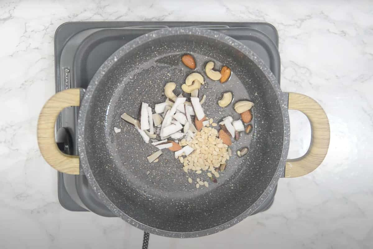 Almonds, cashew nuts, pistachios, melon seeds, flax seeds, and coconut added in the pan.