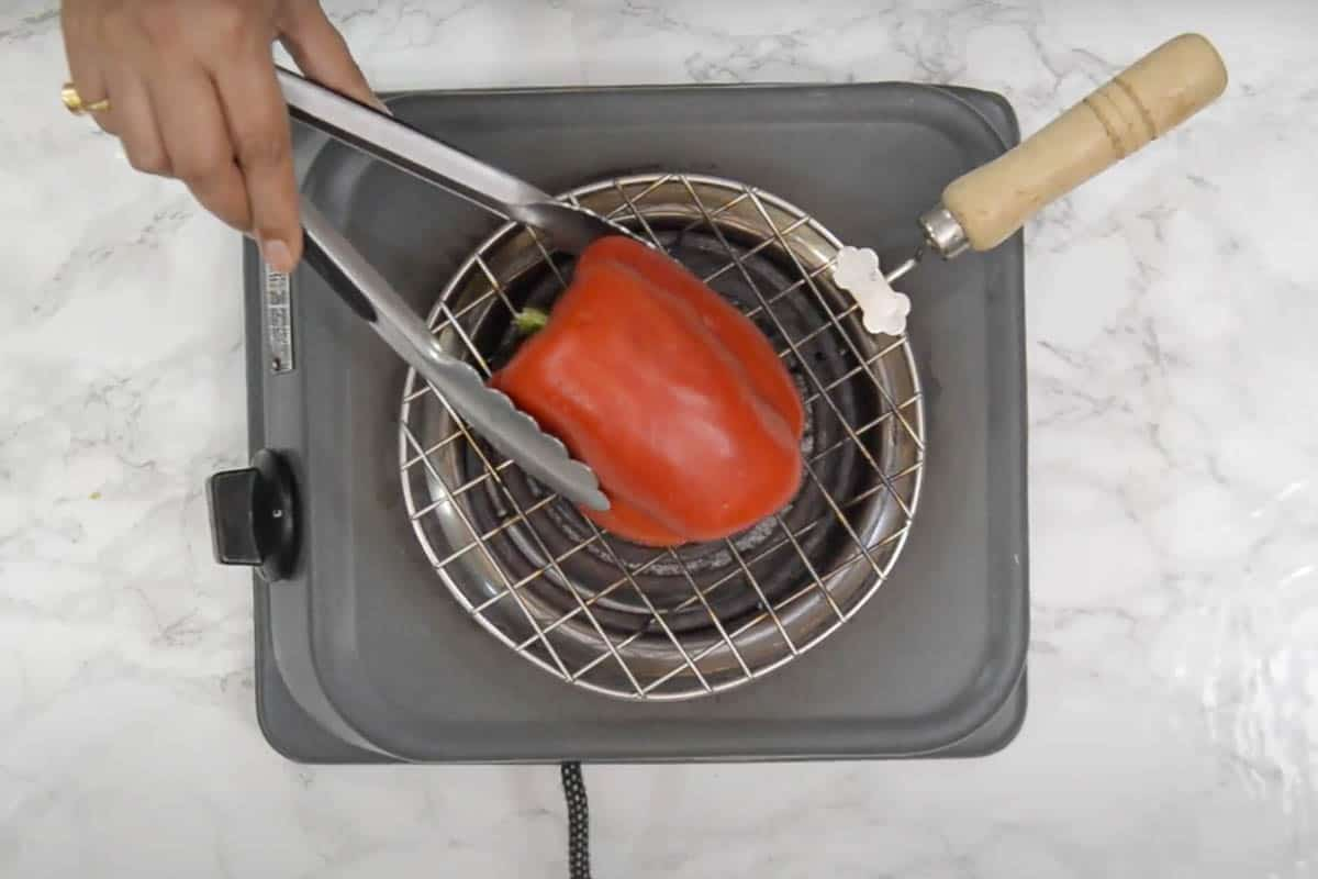 red bell pepper roasting over direct flame.