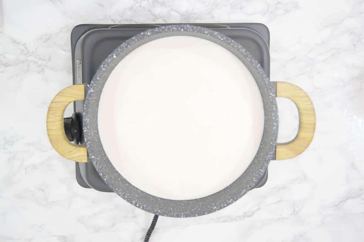 More milk heating in a pan.