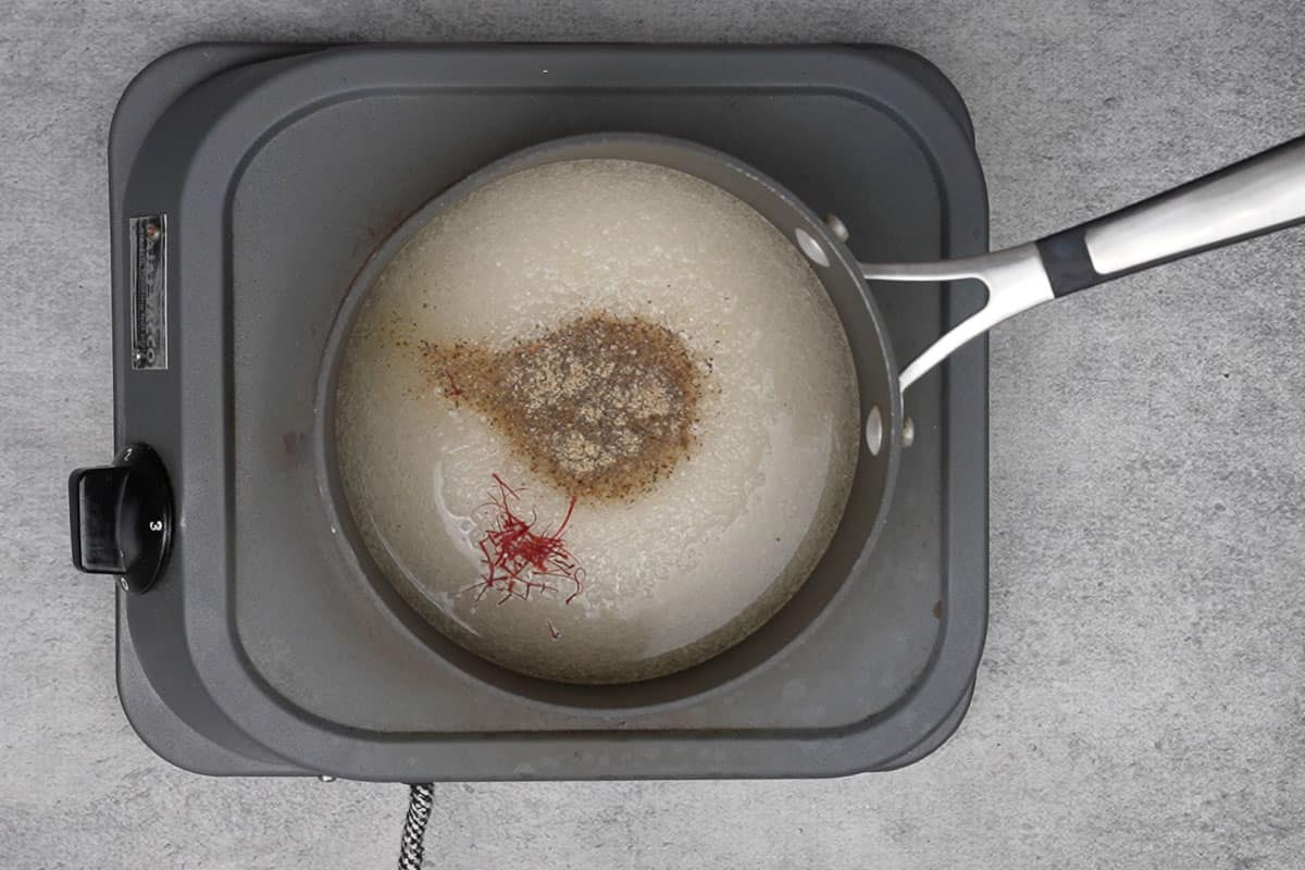 Sugar, water, cardamom powder and saffron added to a pan.