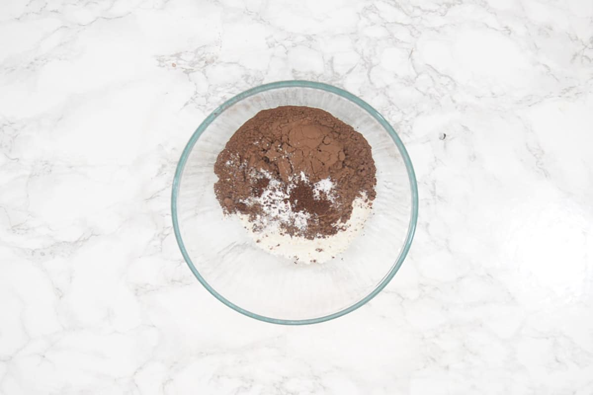 All purpose flour, cocoa powder, salt, baking powder and coffee powder added in a bowl.