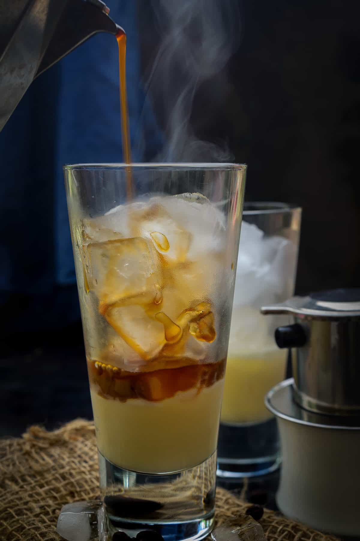 Brewed coffee pouring over the ice in a glass.