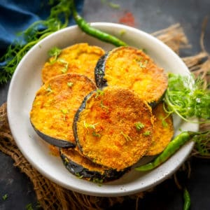Bengali Begun Bhaja or Baingan Bhaja is a dish prepared out of thick slices of the eggplant marinated in spices and coated with rice flour and deep-fried. It goes perfectly with rice and dal and even phulka.