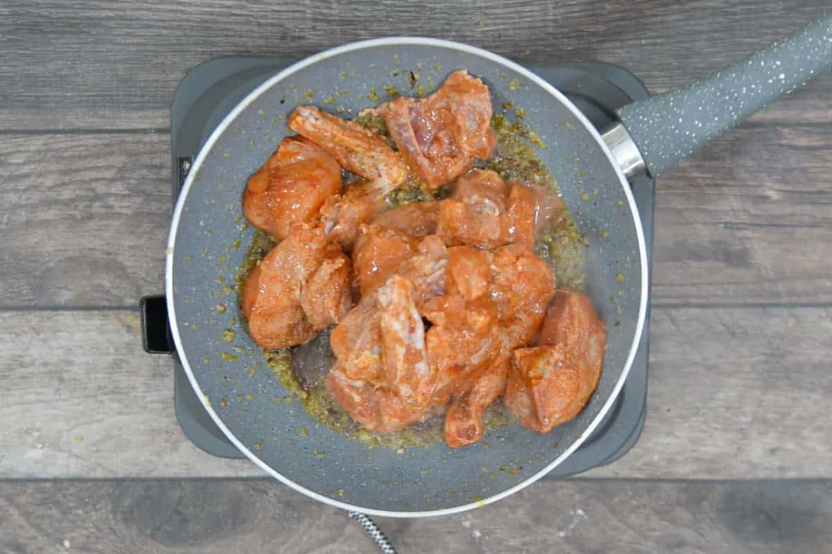 Marinated chicken added to the pan.