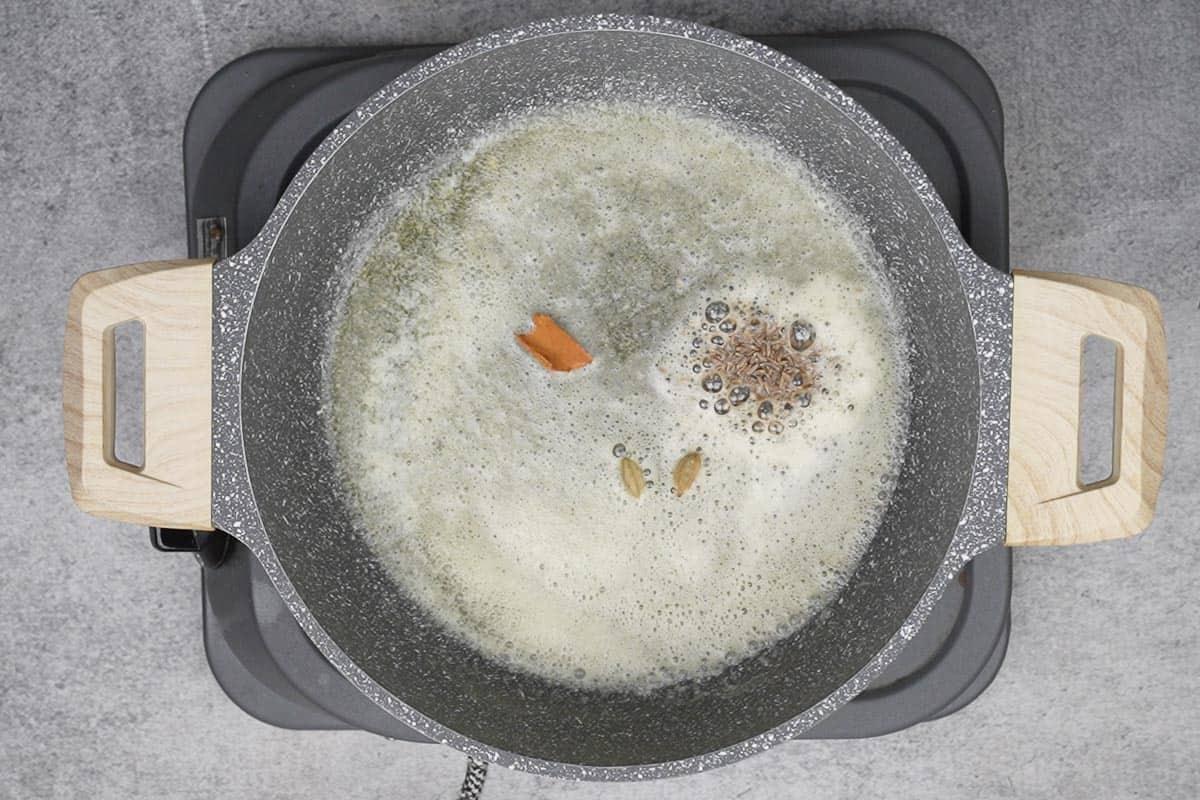 Cumin seeds, cinnamon and green cardamoms added to the pan.