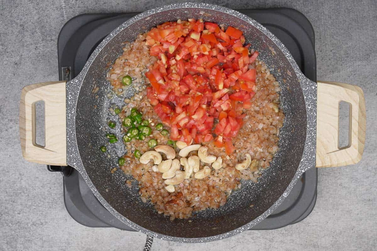 Tomatoes, green chilies and cashew nuts added to the pan.