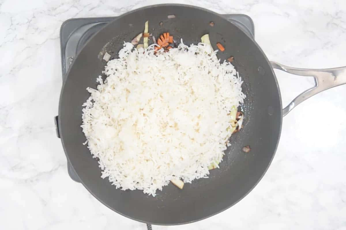 Cooked rice added to the wok.