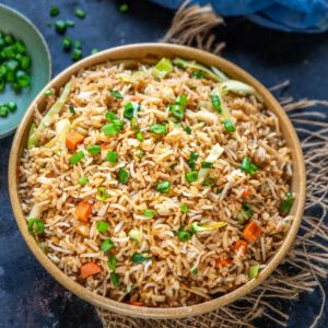 Make this Chinese restaurant-style vegetable fried rice in 20 minutes. It is quick, easy to make, and customizable. Serve it as a side dish or a main course by itself.