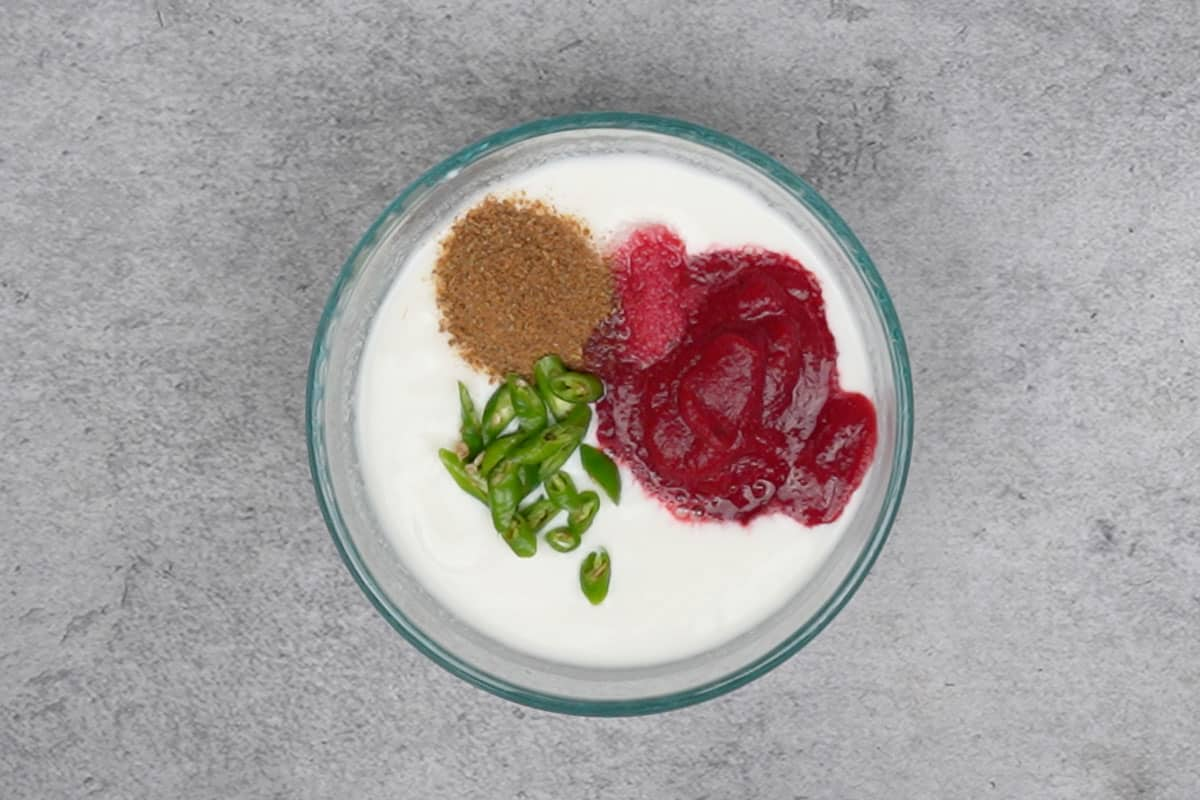 Beetrot puree, salt, cumin powder and green chilies added to the bowl.