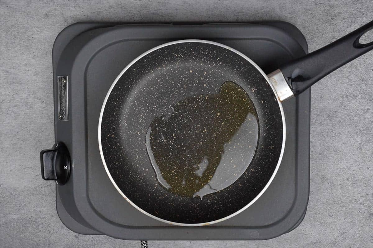 Oil for tempering heating in a skillet.