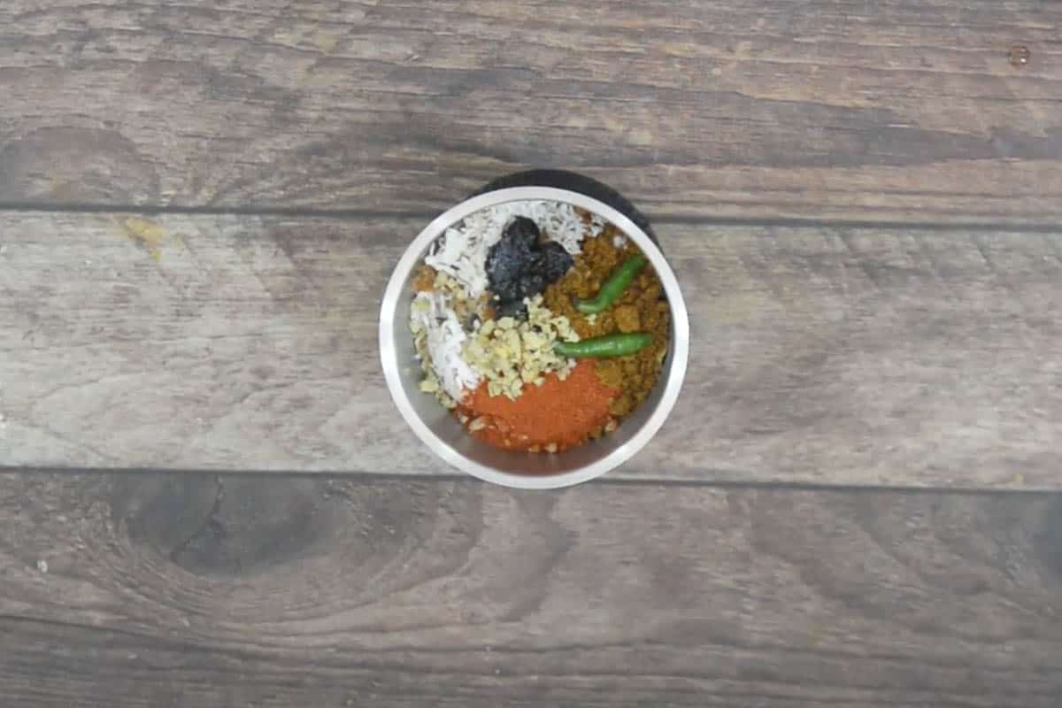 Peanuts, coconut, jaggery, goda masala, tamarind paste, red chili powder, green chilies, ginger, onion, and ¼ cup water added to a grinder.